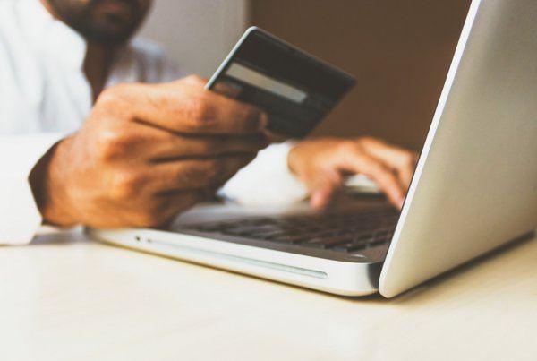 man met creditcard achter laptop